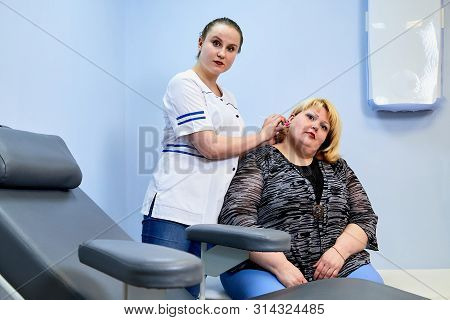 Young Inexperienced Female Doctor Taking Care Of A Fat Sick Woman On The Couch In The Medical Office