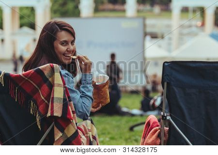 Woman Eating Chips Sitting In Camp-chair Looking Movie In Open Air Cinema Lifestyle Concept