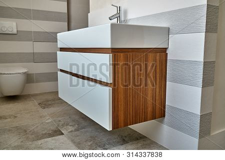 Wall mounted bathroom vanity in luxury bathroom with striped tiles. Stylish interior of modern bathroom. Details furniture