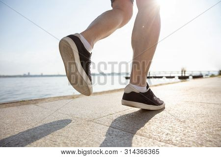 Senior Man As Runner With Armband Or Fitness Tracker At The Riverside. Caucasian Male Model Practici