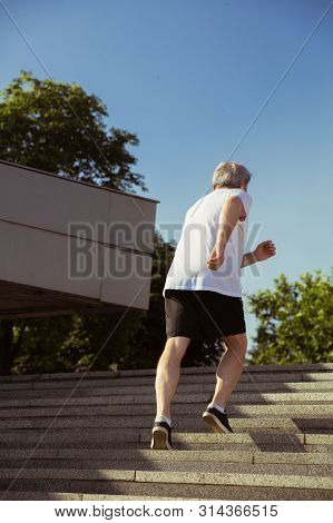 Senior man as runner with armband or fitness tracker at the citys street. Caucasian male model practicing jogging and cardio trainings in summers morning. Healthy lifestyle, sport, activity concept. poster