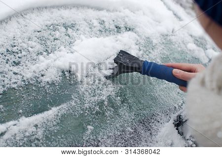 Scraping Snow From The Car Window. Scraping Ice And Snow From The Car Window