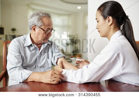 Asian Female Doctor In White Coat Making A Vaccination From Flu To The Senior Man While They Sitting