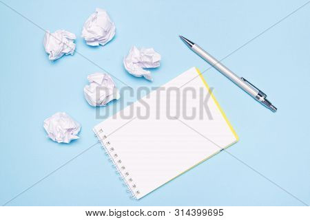 Open Empty Notebook, Pen And Crumpled Paper Balls On Blue Paper Background. Creation Process, Idea O