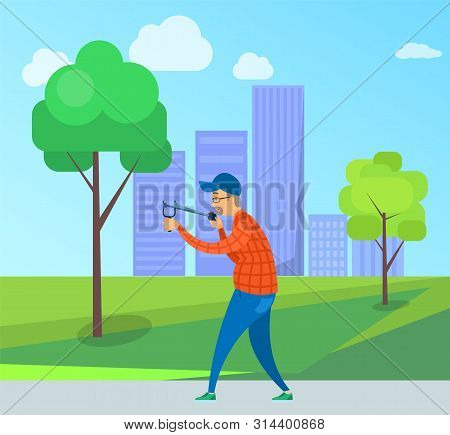 Smiling Elderly Male Targeting With Slingshot, Side And Full Length View Of Aged Man Wearing Casual
