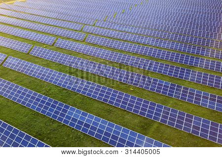 Large field of solar photo voltaic panels system producing renewable clean energy on green grass background. poster