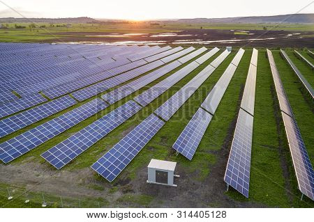 Blue solar photo voltaic panels system producing renewable clean energy on rural landscape and setting sun background. poster