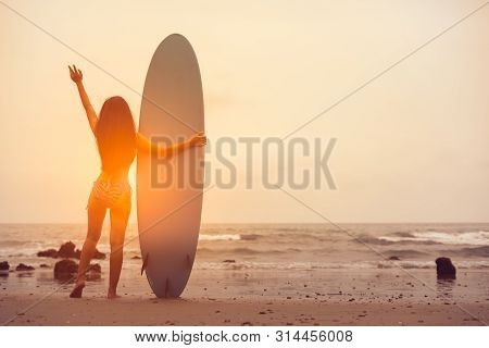 View Of Beautiful Sexy Young Woman Surfer Girl In Bikini With Blue Surfboard On A Beach At Sunset Or