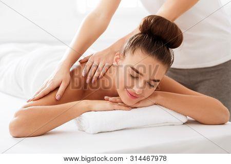 Body Massage. Woman Enjoying Shoulder Massage In Light Spa Salon