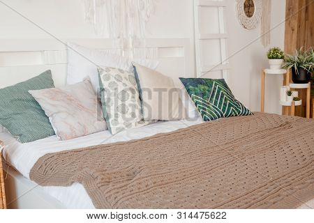 Green, Beige Pillow On Bed In Bedroom With Pastel Colored Bedsheets On Bed. Stylish White Apartment