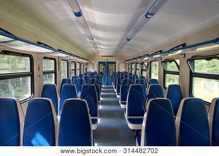 Empty Suburban Train. Blue Chairs. Gorizontal Photo