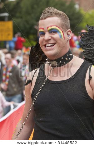 Festival goers with painted faces hold the rainbow banner at the Exeter Pride