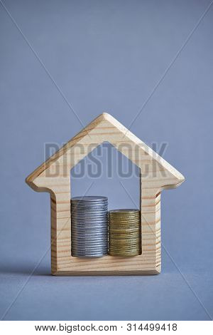 Wooden Figurine Of House And Two Columns Of Coins Inside On Gray Background, The Concept Of Buying O