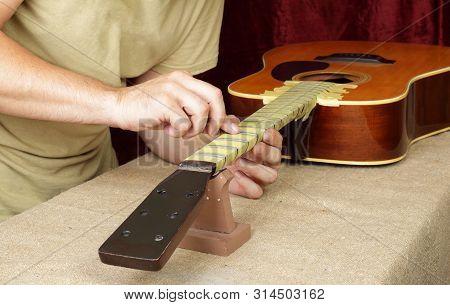 Musical Instrument Guitar Repair And Service - Worker Polishing Guitar Neck Frets Acoustic Guitar Sa