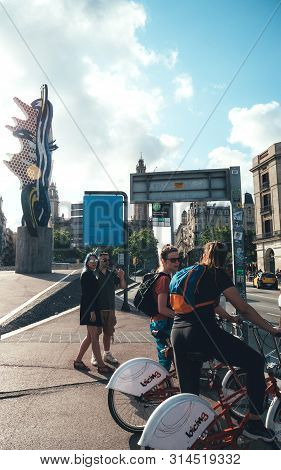 Barcelona, Spain - Jun 1, 2018: Vertical Image Of Cyclists Women Waiting To Cross The Busy Pas Sota