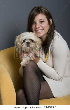 Young beautiful female brunette sitting in yellow chair with her lowchen dog. poster