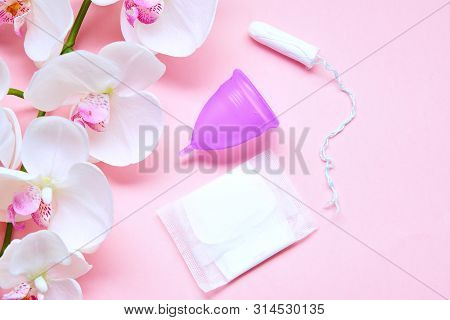 Various Sanitary Products On Pastel Pink Background. Pad, Menstrual Cup, Tampons. Perion Concept. Fl