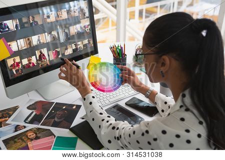 High angle view of pretty mixed-race female graphic designer working on computer and holding colour swatch at desk in office. Modern casual creative business concept