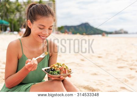 Woman eating poke bowl of ahi tuna on waikiki beach Hawaii. Local food fish salad vacation travel. Asian girl happy healthy eat.
