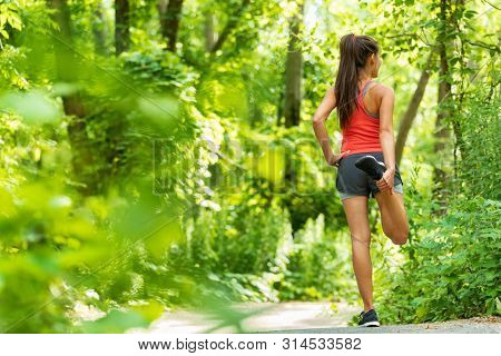 Fit stretch woman stretching quad leg muscle standing getting ready to run jogging outside in summer nature forest park green trees background. Fitness runner athlete running girl.