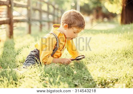 Cute Adorable Caucasian Boy Looking At Plants Grass In Park Through Magnifying Glass. Kid With Loupe