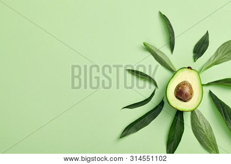 Slices of avocado on color background. Whole and half with Leaves. Simple and minimal food Top View. Creative summer food concept. Abstract lights of avocado sun. Green avocadoes minimal flat lay