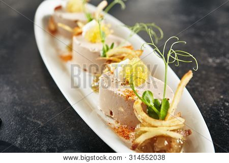 Exquisite Serving White Restaurant Plate with Mousse of Cod Liver, Onion and Crispy Chips  Clsoe Up. Stylish Italian Seafood Dish on Natural Dark Stone, Leaves, Flowers and Fruits Background poster