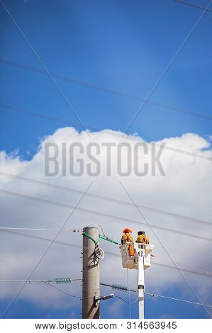 Two Men Hoisted High In The Sky Repairing Faulty Electricity Power Lines