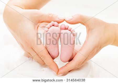 Newborn Baby Feet In Mother Hands Heart, Mom And New Born Kid Foot, Love And Health Care