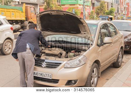 Bengaluru, India June 27,2019 : Businessman Trying To Insepct His Broken Car On Road Side At Bengalu