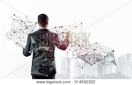 Businessman With Documents Pointing On Abstract Network With Polygonal Shapes. Back View Of Standing