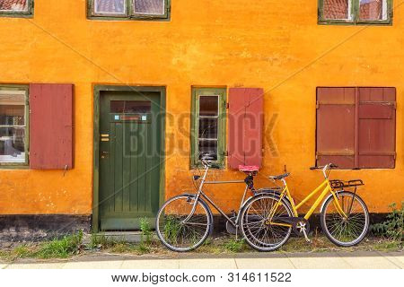 Picturesque of Copenhagen. Old yellow house of Nyboder district with bikes. Old Medieval district in Copenhagen, Denmark poster