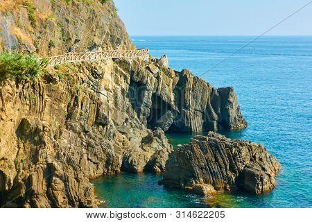 Rocky coast near Riomaggiore with the Love Road (Via dell'Amore) in Cinque Terre, Italy.