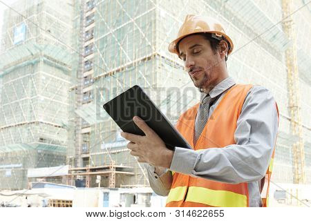 Serious Young Architect In Hardhat And Reflective Vest Standing Outdoors And Working Online On Digit