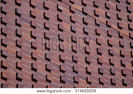 Dark Red, Burgundy Wall With Protruding Bricks , Texture Of Stone And Concrete. Structure, Backgroun