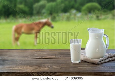 Fresh Koumiss Milk In Glass On Wooden Table And Blurred Landscape With Horse On Green Summer Meadow.