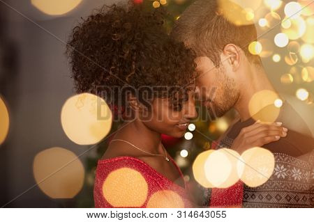 Romantic couple in sweaters dancing before new year eve at home. Young lovely man and african woman hugging over christmas bokeh lights. Multiethnic couple dancing in love with golden lights bokeh.