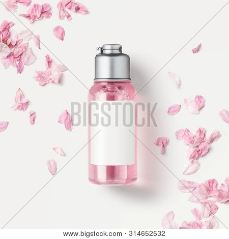 cosmetics / skin care product packaging design concept or mockup with small bottle with pink liquid soap or shower gel surrounded by delicate pink flower petals, blank white label for your design