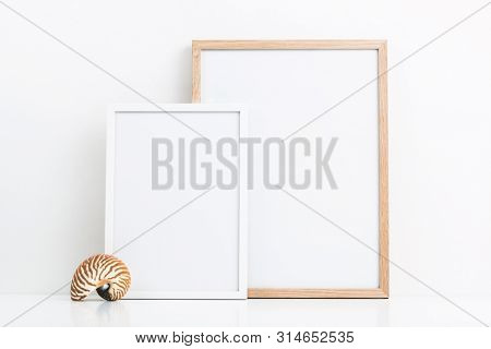 minimal marine / ocean or summer themed mockup with two photo frames and a decorative nautilus shell on a white table, clipping path included, sizes: 30 x 40 cm, 21 x 30 cm