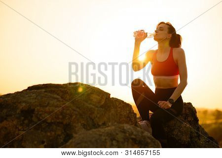 Young Woman Resting and Drinking Water after Trail Running Outdoor. Workout Exercise at Hot Beautiful Summer Sunset. Sport and Healthy Active Lifesyle Concept.