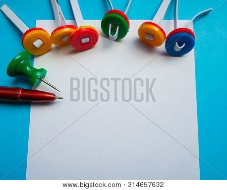 Multi-colored Paper Clips And A White Sheet Of Paper With A Red Pen. View From Above. Concept Back T