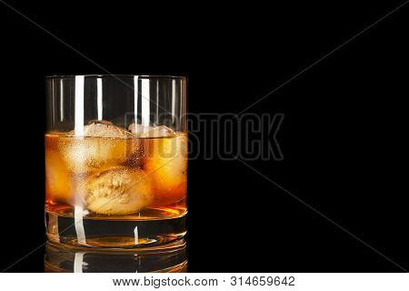 Bourbon Snifter Whiskey Scotch Glass On The Black Background, Copy Space