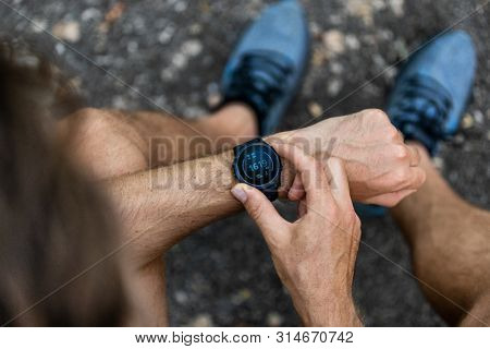 Fit man checking smart watch wearable technology sport smartwatch on fitness run walk outside. Top view from above with running shoes in street.