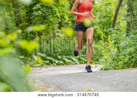 Running athlete woman on run path jogging closeup of lower body thighs, legs, running shoes in forest.