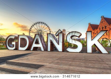 Beautiful architecture of Gdansk with an outdoor sign at sunrise, Poland