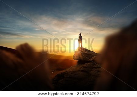 Leadership And Goals. A Man Standning On Top Of A Mountain Watching The Sun Set. Conceptual Photo Co
