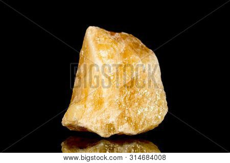 Raw orange calcite mineral stone in front of black background, mineralogy and esotericism poster