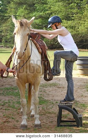 young woman mounting horse
