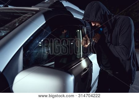 Thief Intruding Car With Flashlight And Crowbar At Night