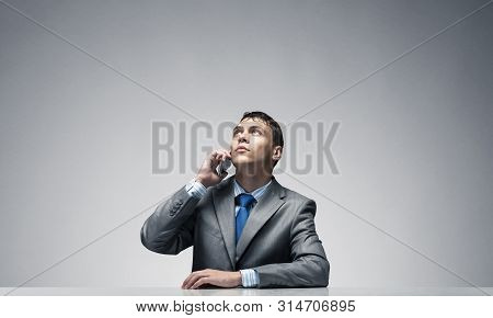 Young Man Talking On Phone And Looking Upward. Businessman Sitting At Desk On Grey Wall Background.